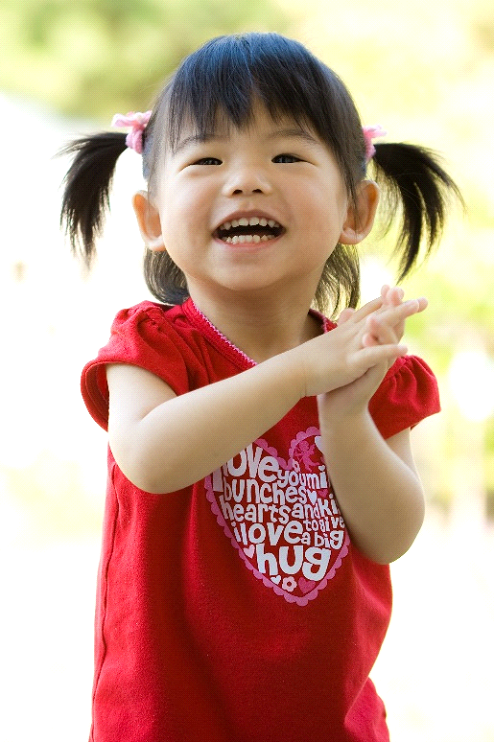 Young girl smiling and holding her hands together.
