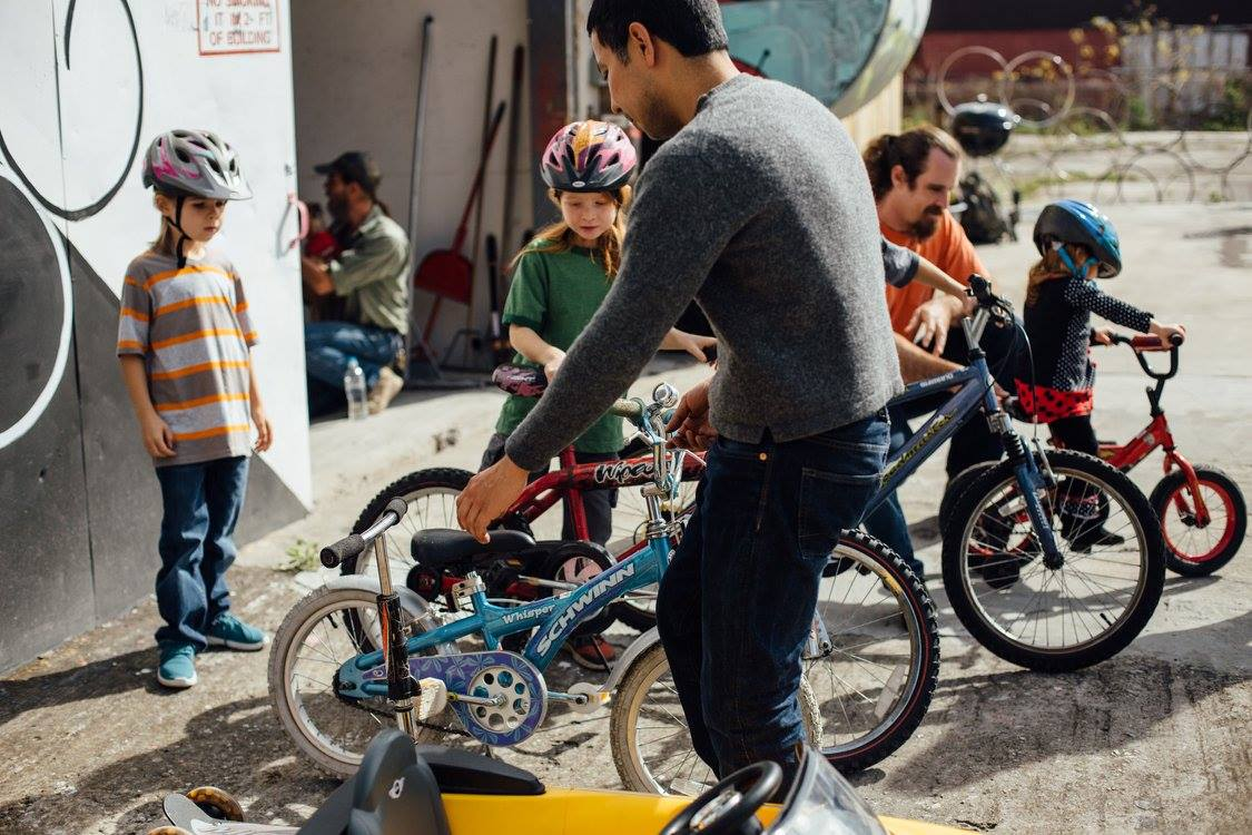 Volunteer assisting children with their bicycles