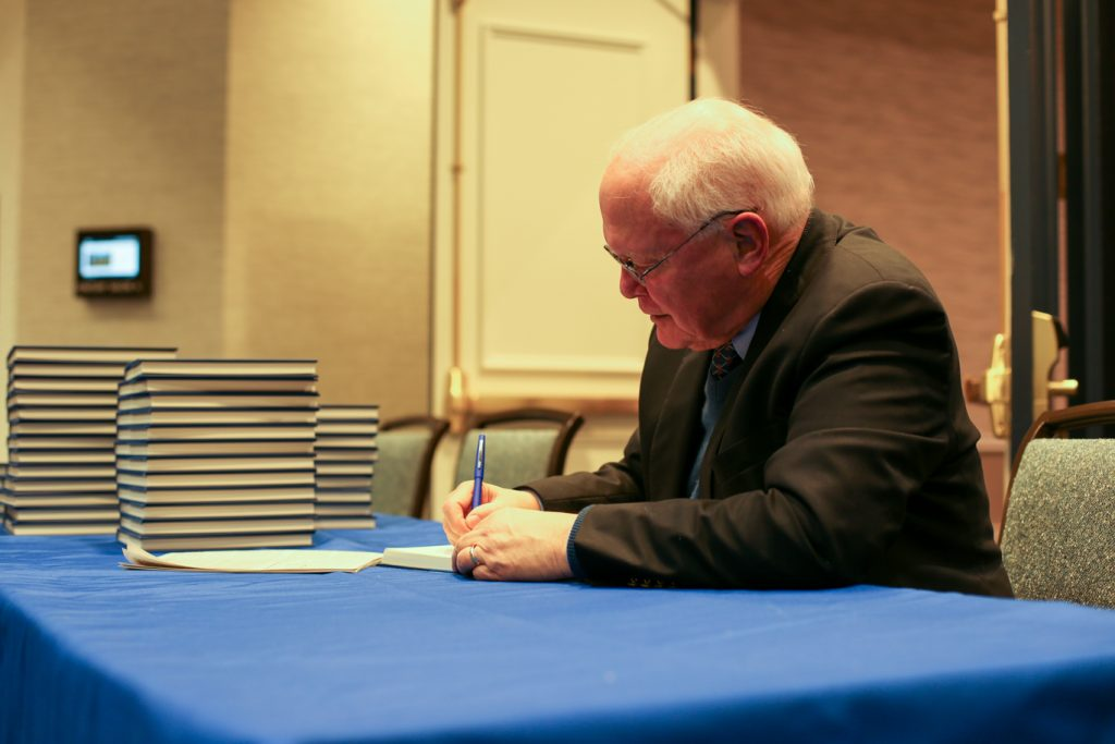 David Lawrence Jr. signing books at a table.
