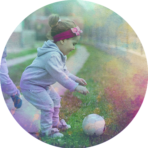 A child picking up a ball on the ground.