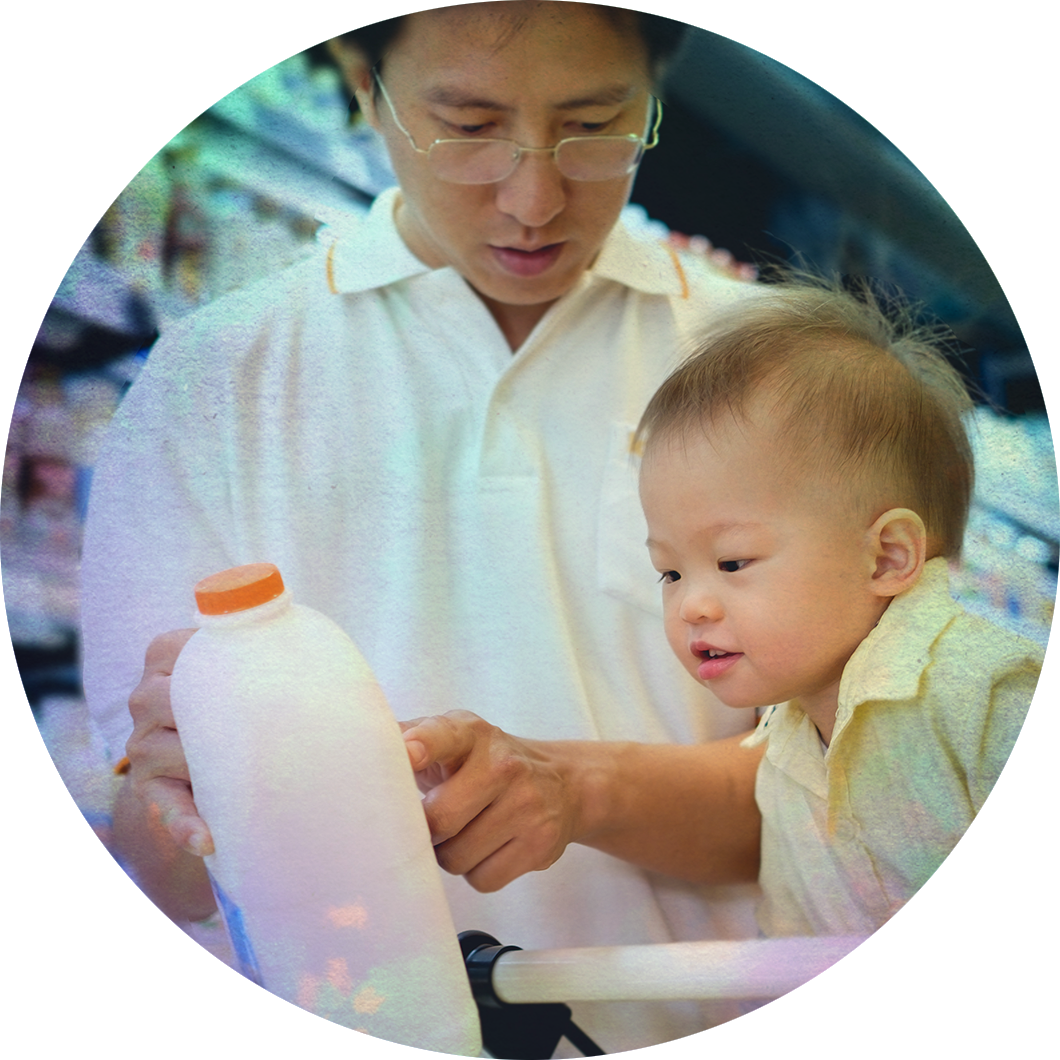 A father picking out milk with his son.
