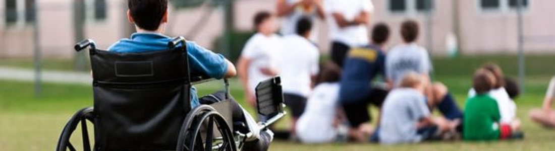 A child in a wheelchair watches a group of children in the distance.