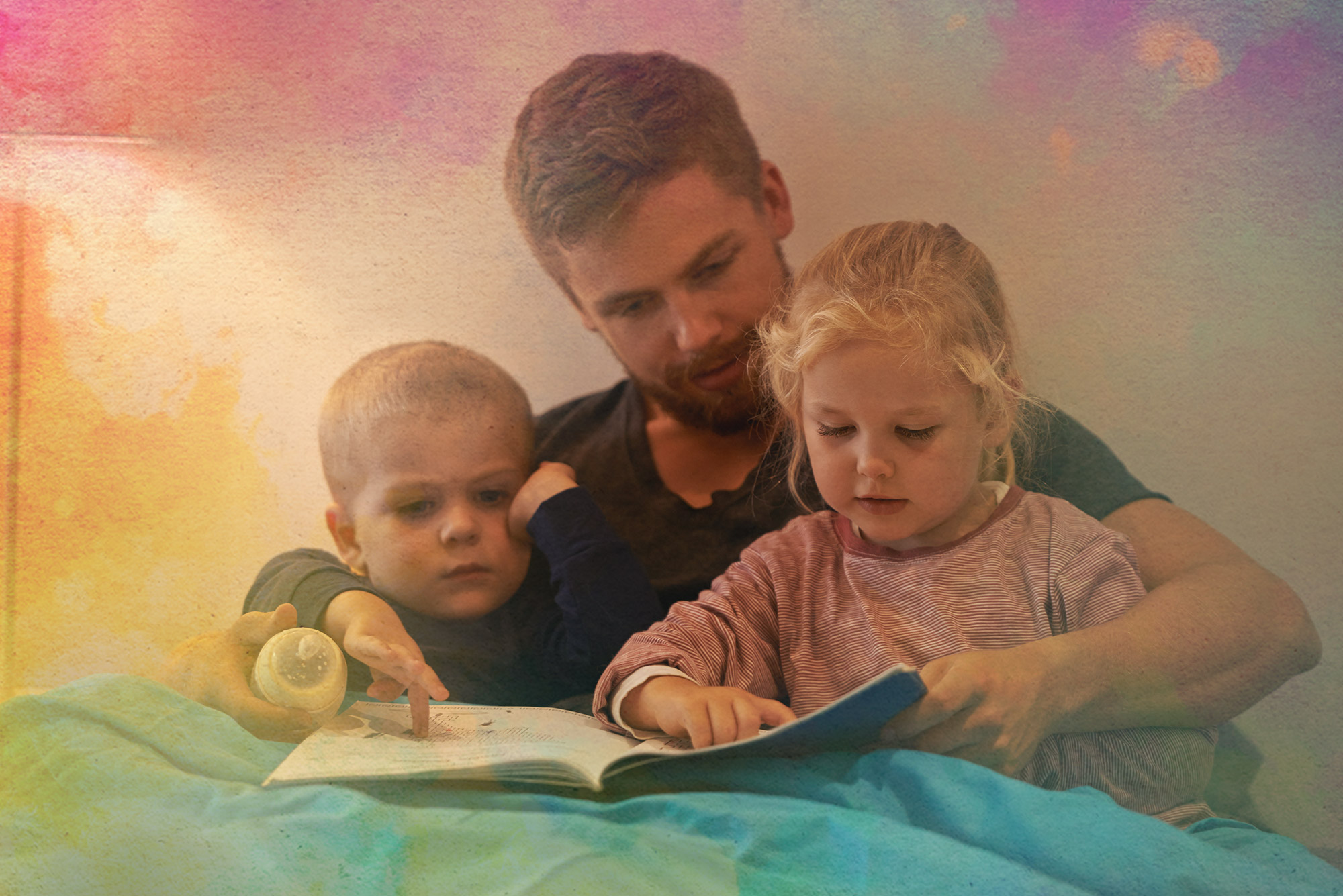 A father reading to his two young children.