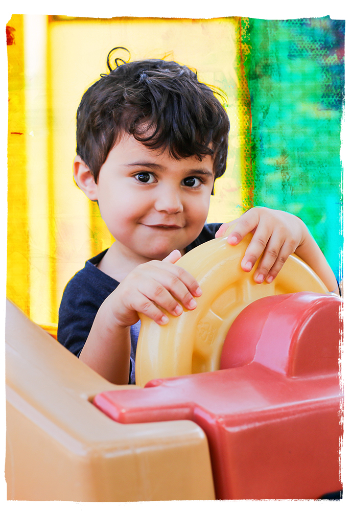 A little boy looking at the camera and holding a wheel on a play set.